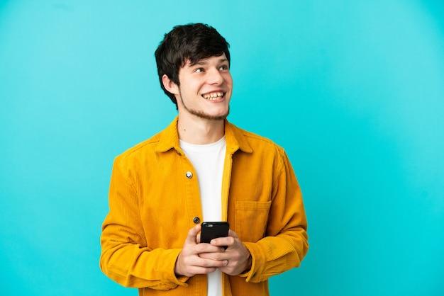 Молодой русский человек изолирован на синем фоне с помощью мобильного телефона и смотрит вверх