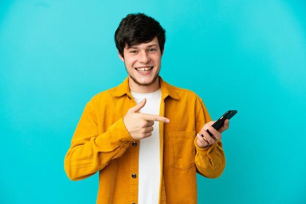 휴대 전화를 사용 하 여 가리키는 파란색 배경에 고립 된 젊은 러시아 남자