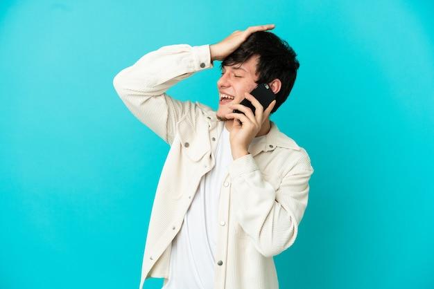 Молодой русский человек, использующий мобильный телефон на синем фоне, кое-что понял и намеревается найти решение