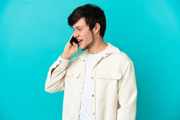 Молодой русский человек с помощью мобильного телефона, изолированные на синем фоне, глядя сторону