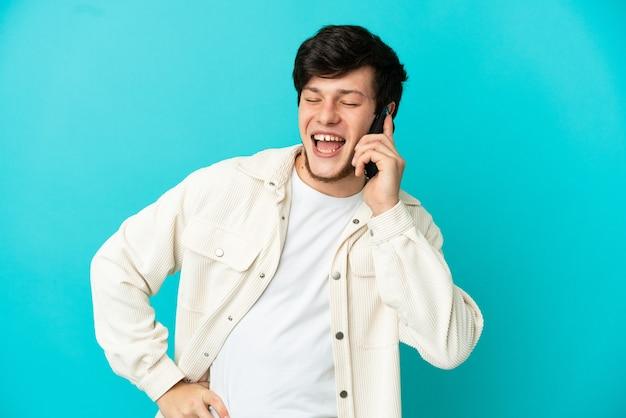 Молодой русский человек с помощью мобильного телефона, изолированные на синем фоне, позирует с руками на бедрах и улыбается
