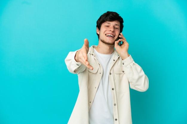 좋은 거래를 닫기 위해 악수 파란색 배경에 고립 된 휴대 전화를 사용하는 젊은 러시아 남자