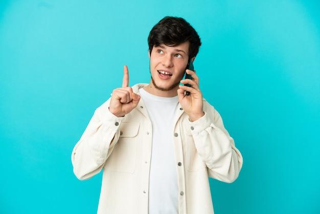 파란색 배경에 격리된 휴대전화를 사용하는 러시아 청년은 손가락을 가리키는 아이디어를 생각하고 있다