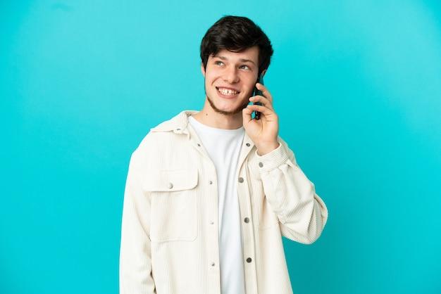파란색 배경에 격리된 휴대전화를 사용하는 러시아 청년