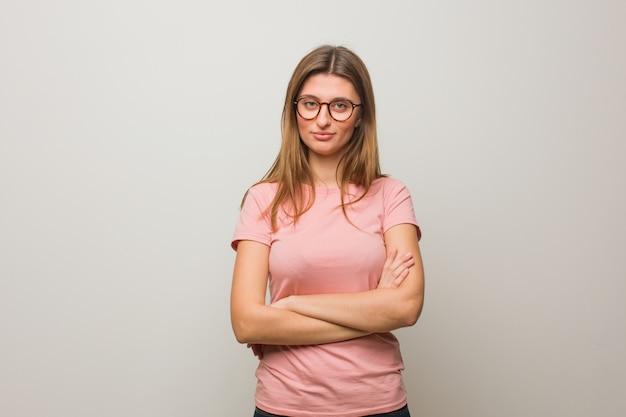 Молодая русская натуральная женщина скрещивает руки, улыбается и расслаблена