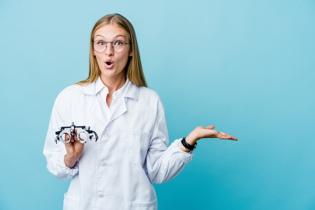 Young russian optometrist woman on blue impressed holding copy space on palm.
