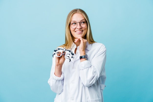 Young russian optometrist woman on blue keeps hands under chin, is looking happily aside.