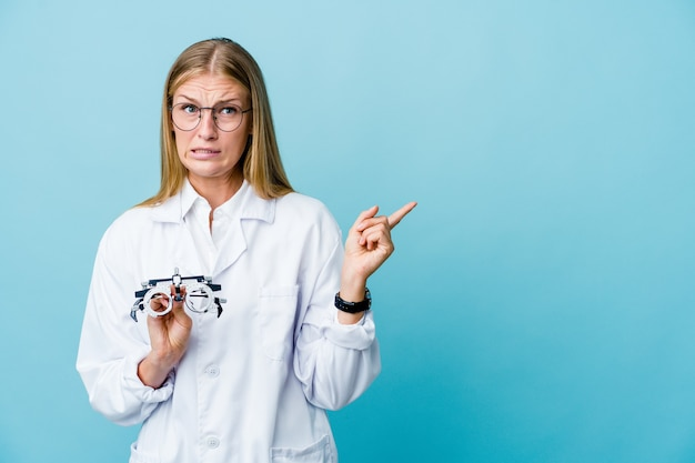 Young russian optometrist woman on blue shocked pointing with index fingers to a copy space.