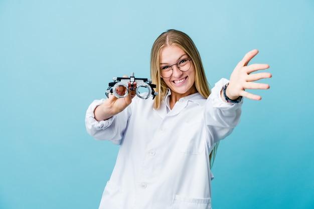 Молодая русская женщина-окулист на синем чувствует себя уверенно, обнимая камеру.