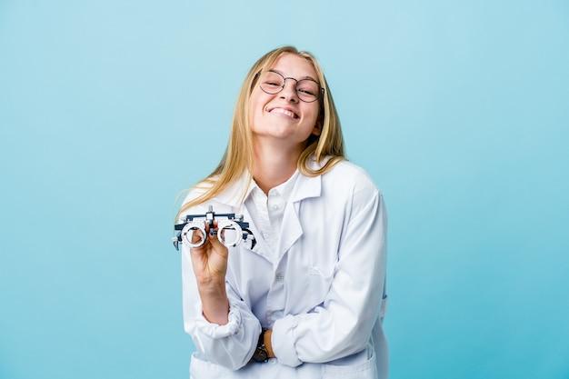 Молодая русская женщина-оптометрист на синем смеется и веселится.