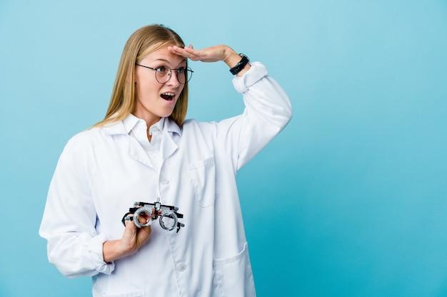 Молодая русская женщина-оптометрист на синем, глядя далеко, держа руку на лбу.
