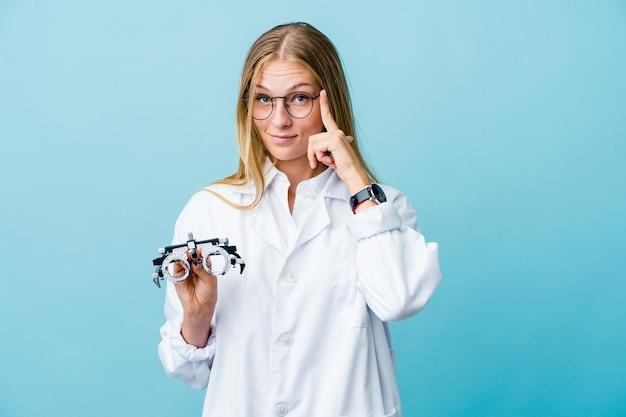 Молодая русская женщина-оптометрист на синем указывающем виске пальцем, думая, сосредоточилась на задаче.