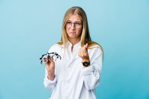 Молодая русская женщина-оптометрист на синем, показывая, что у нее нет денег.