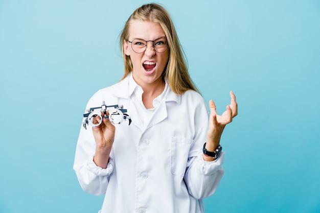 Молодая русская женщина-оптометрист на синем расстройстве кричит напряженными руками.