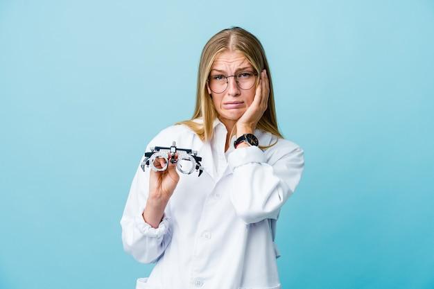 Молодая русская женщина-оптометрист на синем нытье и безутешно плачет.
