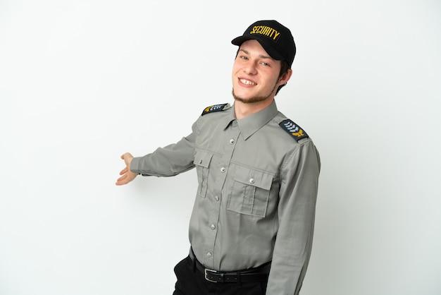 Молодой российский охранник изолирован на белом фоне, протягивая руки в сторону для приглашения приехать