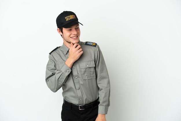 Молодой российский охранник изолирован на белом фоне, глядя в сторону и улыбается