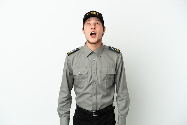 Молодой российский охранник изолирован на белом фоне, глядя вверх и с удивленным выражением лица
