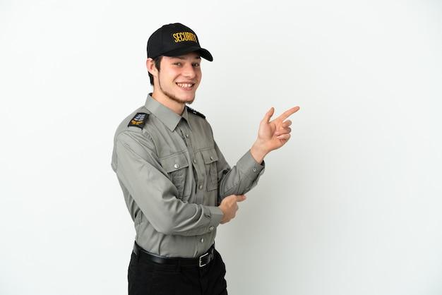 Молодой российский охранник изолирован на белом фоне, указывая пальцем в сторону