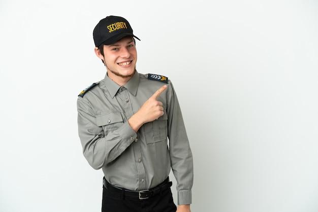 Молодой российский охранник изолирован на белом фоне, указывая в сторону, чтобы представить продукт