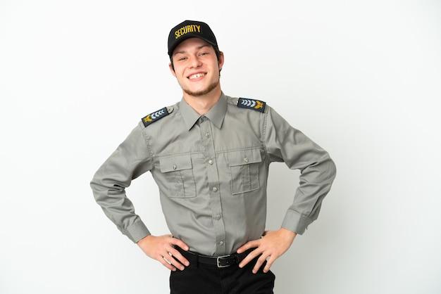 Молодой российский охранник изолирован на белом фоне позирует с руками на бедрах и улыбается
