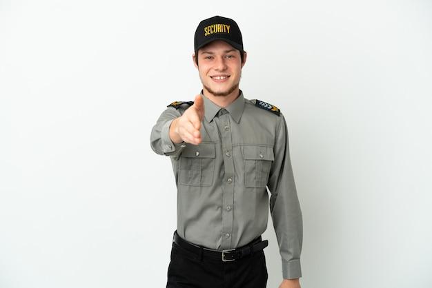 Молодой российский охранник изолирован на белом фоне, пожимая руку для заключения хорошей сделки