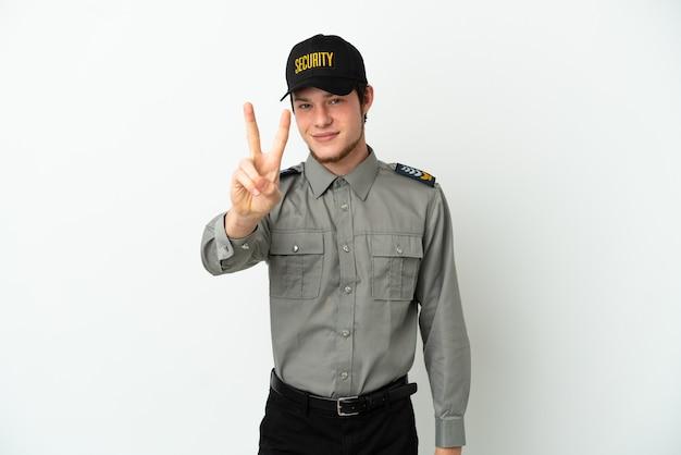 Молодой российский охранник изолирован на белом фоне, улыбаясь и показывая знак победы