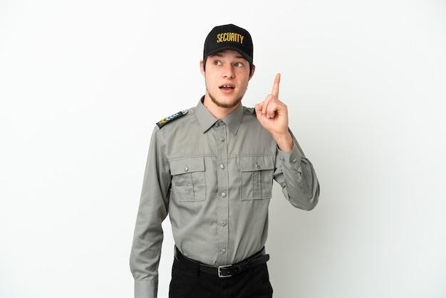 Молодой российский охранник изолирован на белом фоне, думая об идее, указывая пальцем вверх