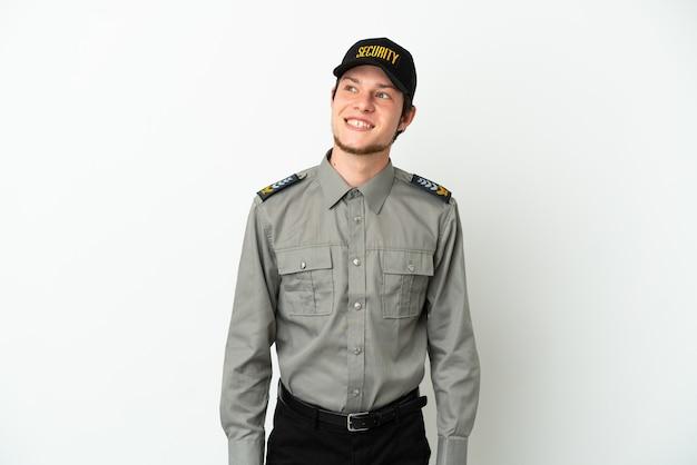 Молодой российский охранник изолирован на белом фоне, думая об идее, глядя вверх