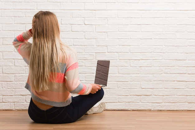 Young russian student woman sitting from behind thinking about something
