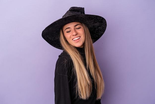 紫色の背景に隔離されたハロウィーンを祝う魔女に変装した若いロシアの女性は、笑顔、陽気で楽しい脇に見えます。