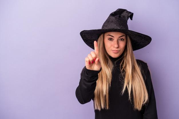 ハロウィーンを祝う魔女に変装した若いロシア人女性は、指でナンバーワンを示す紫色の背景に分離されました。