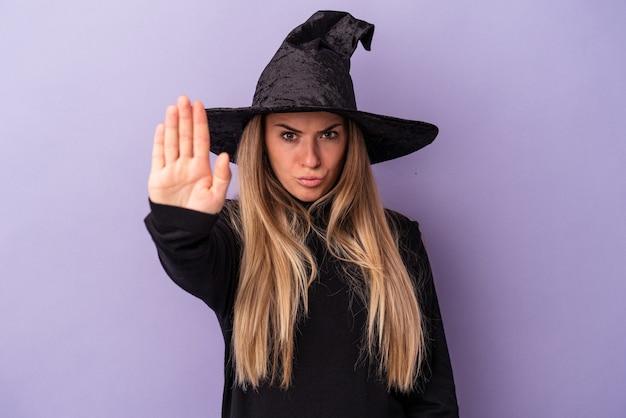 ハロウィーンを祝う魔女に変装した若いロシア人女性が紫色の背景に孤立し、手を伸ばして一時停止の標識を示し、あなたを妨げています。
