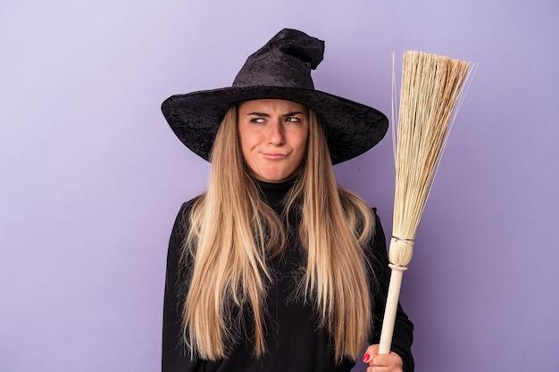 Молодая русская женщина, переодетая ведьмой, держащей веник, изолированную на фиолетовом фоне, смущена, чувствует себя сомневающейся и неуверенной.