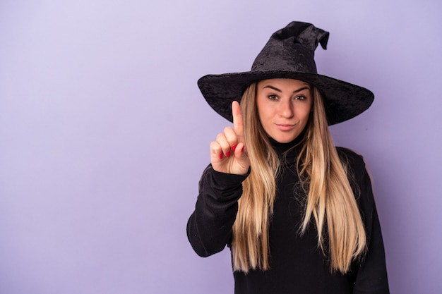 Young russian woman disguised as a witch celebrating halloween isolated on purple background showing number one with finger.