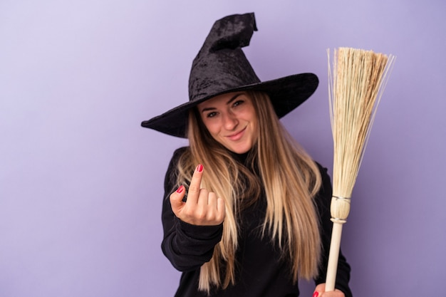 Young russian woman disguised as a witch holding a broom isolated on purple background pointing with finger at you as if inviting come closer.