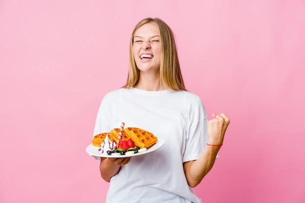 와플을 먹는 젊은 러시아 여자는 평온하고 흥분된 응원을 격리합니다. 승리 개념.