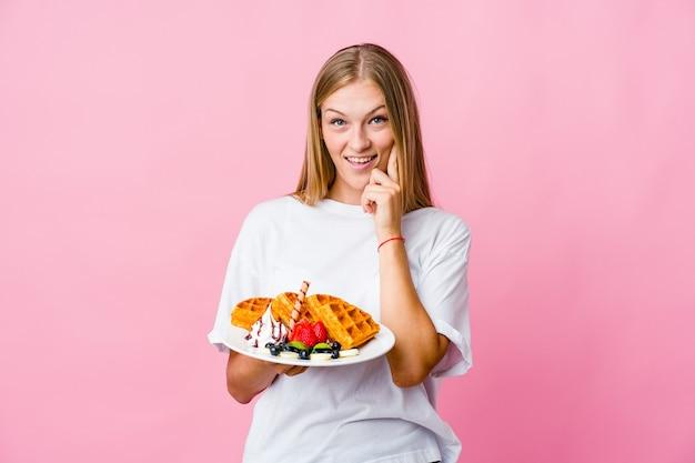 Молодая русская женщина ест вафли, изолированных улыбается, счастливый и уверенный, трогательно подбородок рукой.