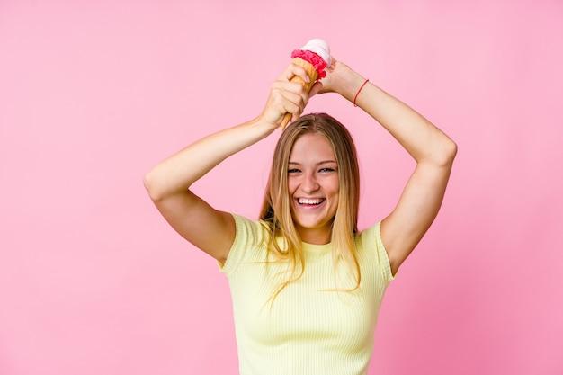 特別な日を祝って孤立したアイスクリームを食べる若いロシアの女性は、エネルギーでジャンプして腕を上げます。