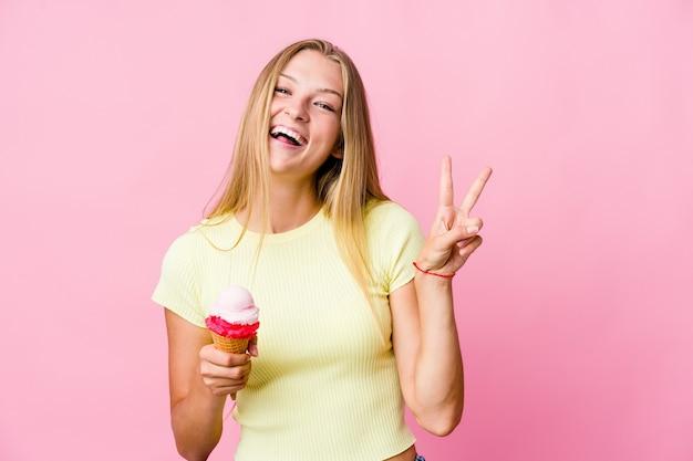 Молодая русская женщина ест мороженое изолированной радостной и беззаботной, показывая пальцами символ мира.