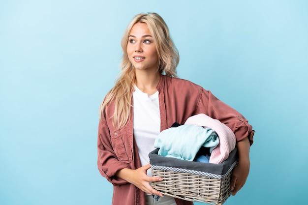 側面を見て青い背景で隔離の服バスケットを保持している若いロシアの女性