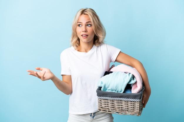 側面を見ながら驚きの表情で青い背景で隔離の服バスケットを保持している若いロシアの女性