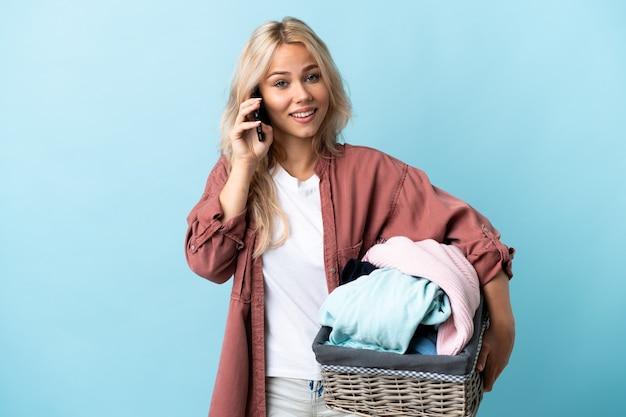 誰かと携帯電話で会話をしながら青で隔離の服のバスケットを保持している若いロシアの女性