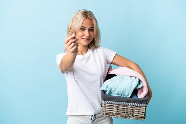 Молодая русская женщина держит корзину с одеждой, изолированную на синем, делая денежный жест