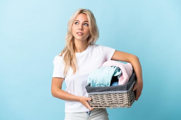 Молодая русская женщина держит корзину с одеждой, изолированную на синем, думая об идее, глядя вверх