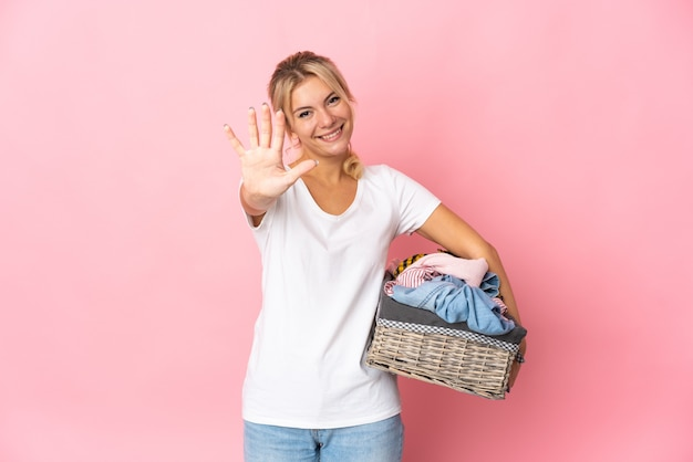손가락으로 5 세 분홍색 배경에 고립 된 옷 바구니를 들고 젊은 러시아 여자