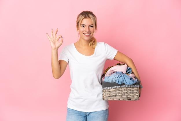 ピンクの背景で隔離の服のバスケットを保持している若いロシアの女性は、指でokサインを示しています
