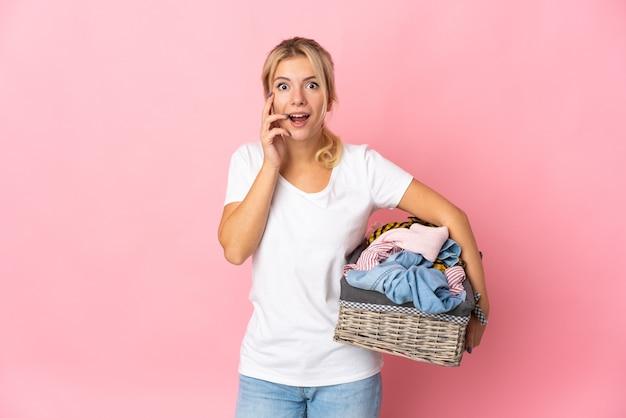 驚きとショックを受けた表情でピンクの背景で隔離の服バスケットを保持している若いロシアの女性