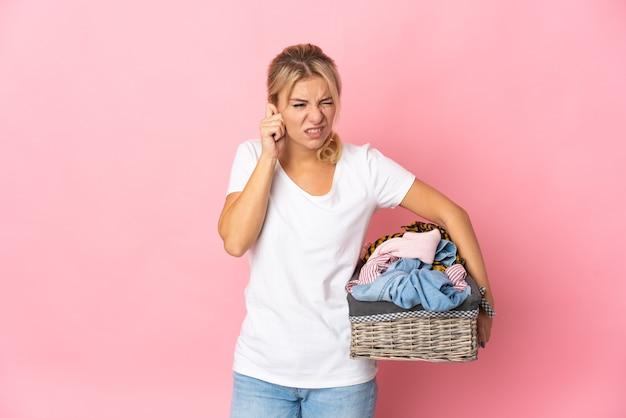 ピンクの欲求不満と耳を覆って隔離の服のバスケットを保持している若いロシアの女性