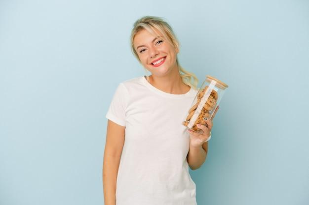 幸せ、笑顔、陽気な青い背景で隔離のクッキーを保持している若いロシアの女性。